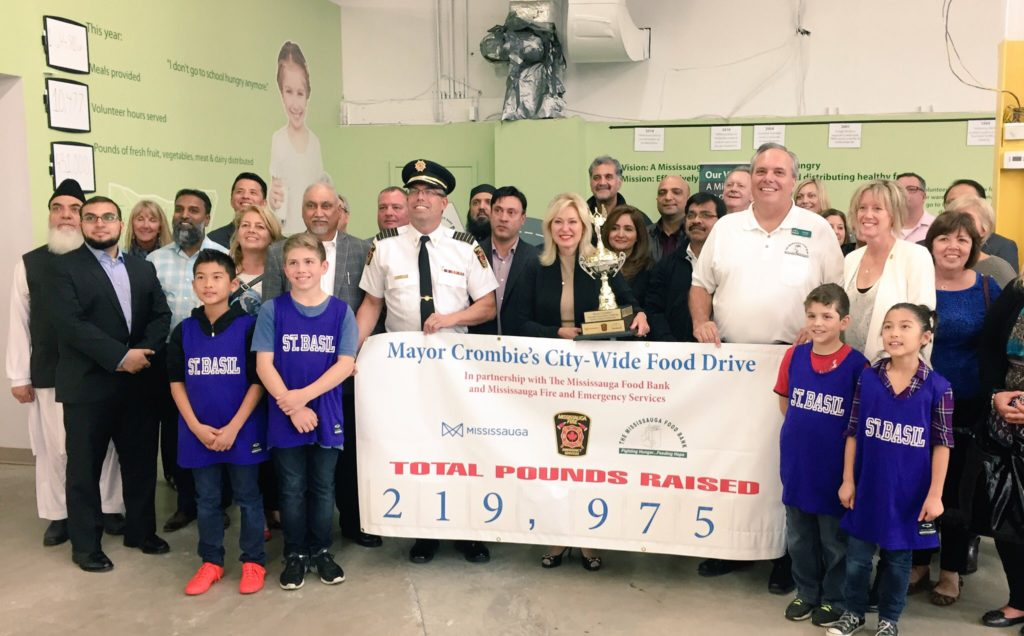 Mayor Crombie joins Chris Hatch, Executive Director of The Mississauga Food Bank, Mississauga Fire and Emergency Services Chief Tim Beckett, and #OneBagChallenge volunteers.